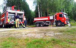 """""""Bild från basplatsen/utgångspunkten där bland annat tankbil, släckbil och terrängfordon stod. Utifrån basplatsen kopplade vi ihop över 1km slang i uppåtsluttande skogsterräng."""" Foto: Karl-Johan Svensson"""